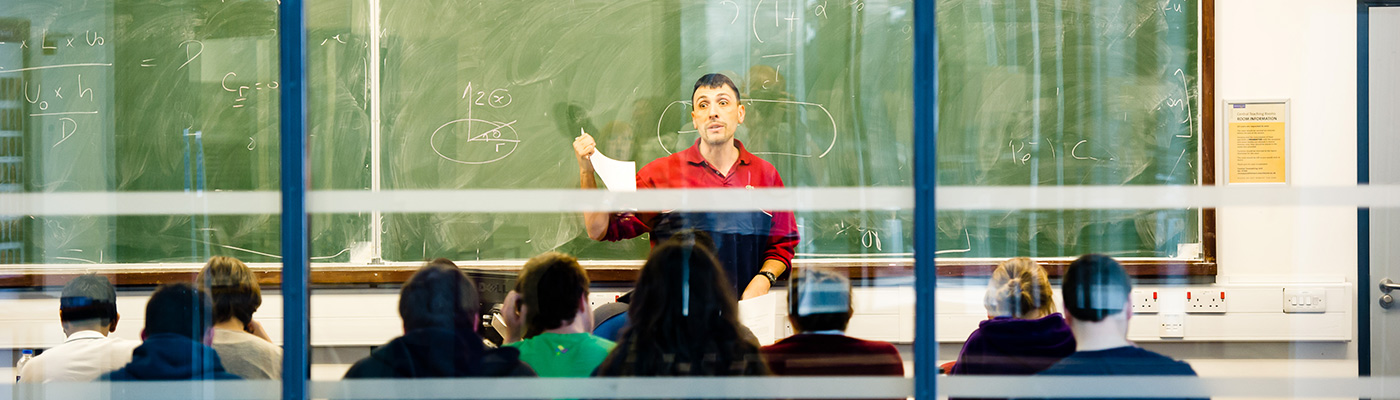 Professor teaching class of students in seminar room