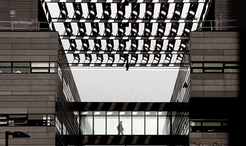 Student walking across walkway in Alan Turing Building