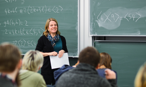 Lecturer stood smiling holding paper in front of green chalkboard
