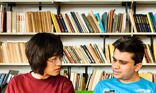 Two students sitting in front of shelves of colourful books