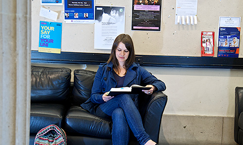 Postgraduate student sat flicking through a book