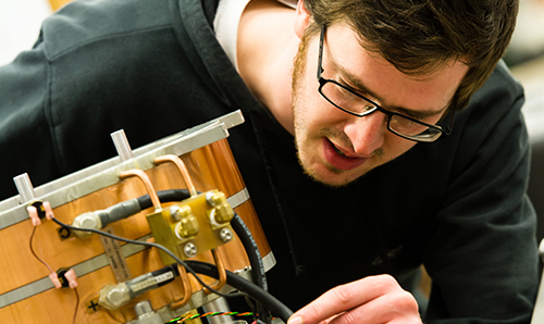 A male maths researcher operating industrial equipment