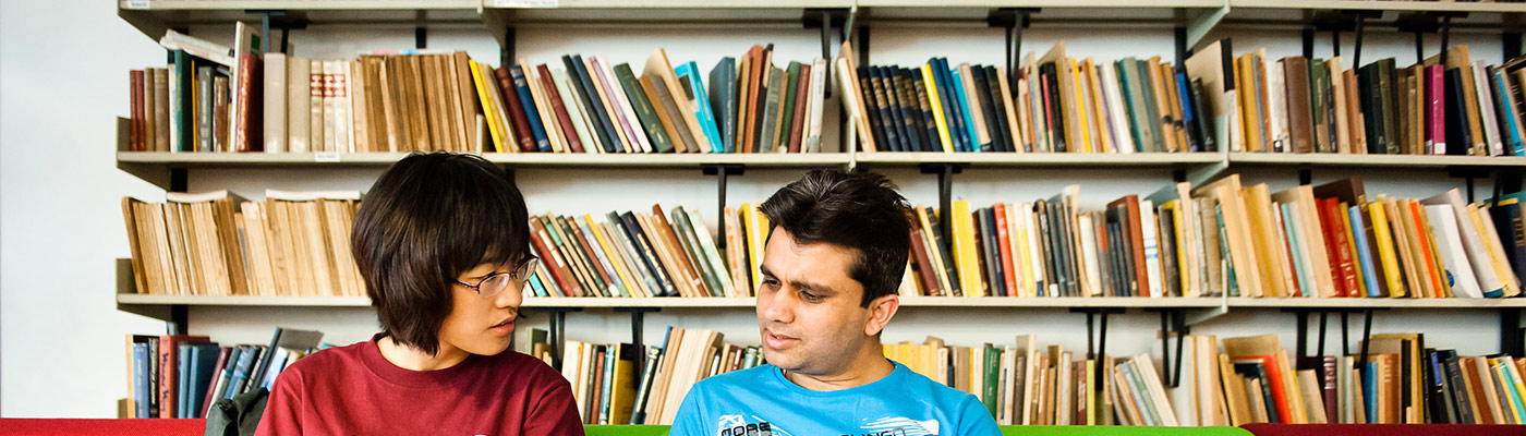 Two students sat in front of shelves of colourful books